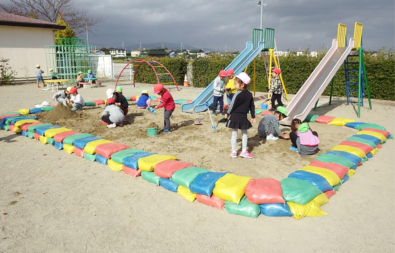 園児と一緒に砂場の再生作業